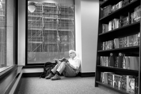 Man sits on floor reading in bookstore