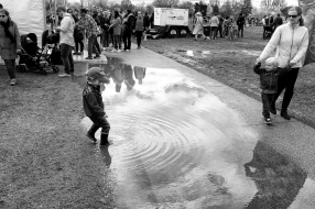 little boy steps into big puddle