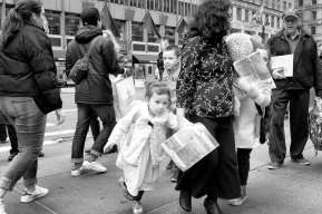 young girls propelled by mother through crowded street