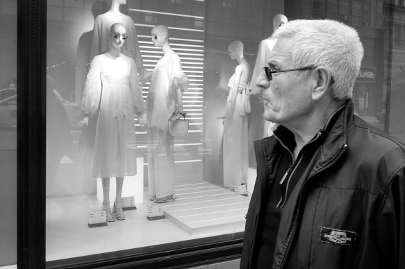 Fashionable man in glasses against backdrop of NYC fashion window