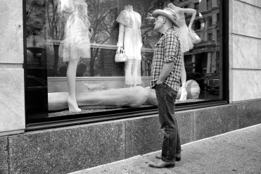 Man in cowboy boots and hat looks in NYC store window at women's fashion